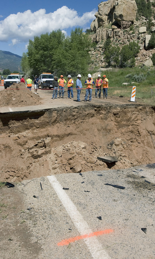 Al Hartmann  |  The Salt Lake Tribune Road contractors check out a 25-foot-deep 40-foot-wide hole on Highway 35 about 3 miles south of Tabiona on Thursday morning. A Tabiona girl was killed and two people injured when their vehicles encountered the washed-out road Wednesday night.