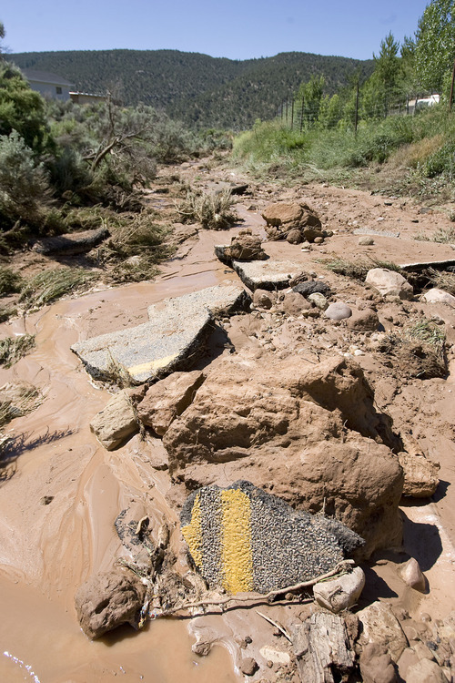 Al Hartmann  |  The Salt Lake Tribune Pieces of asphalt from State Road 35 lie downstream from the 25-foot-deep, 40-foot-wide washout Thursday morning. A Tabiona girl was killed and two people injured when their vehicles encountered the washed-out road Wednesday night.
