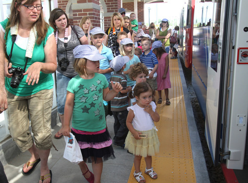 Rick Egan   |  The Salt Lake Tribune Parents and children ride the new TRAX Mid-Jordan line to Daybreak from Gardner Village on Friday. The test ride was offered to