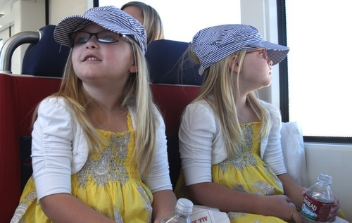 Rick Egan      The Salt Lake Tribune Twins, Emberly and Jocelynn Smith, 5, Magna, wear engineer caps as they ride the new Mid-Jordan TRAX line to Daybreak from Gardner Village on Friday. The test ride was offered to