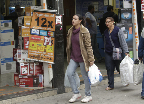In this July 7, 2011 photo, people walk through a shopping district in Sao Paulo, Brazil. The Central Bank expects that by the end of the year, 28 percent of Brazilians' disposable income will go toward servicing debts, compared to 16 percent in the still-recovering U.S. and single-digit figures in other developing nations. The bank also reports that 28 million Brazilians out of a population of 190 million are carrying more than $3,000 in debt, up 250 percent from six years ago. Some economists fear that these consumers have taken on too much debt and are being buried by Brazil's sky-high lending rates. They worry that if debt erodes their buying power, Brazil might face a recession. (AP Photo/Andre Penner)