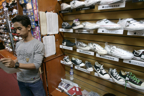 Irwin Fedriansyah  |  The Associated Press A shop attendant stands near Converse shoes on display at a store in Jakarta, Indonesia. Workers making Converse sneakers in Indonesia said supervisors throw shoes at them, slap them in the face and call them dogs and pigs. Nike, the brand's owner, admits that such abuses have occurred among the contractors that make its hip high-tops but claims there was little it could do to stop it.
