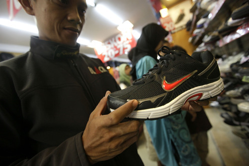 Dita Alangkara  |  The Associated Press An Indonesian man inspects a Nike shoe at a store in Jakarta, Indonesia, May 17. Workers for a Nike contractor in Indonesia say they've been physically and verbally abused for several years, with supervisors calling them