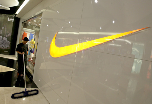 Dita Alangkara  |  The Associated Press Ajanitor sweeps the floor outside a Nike store at a shopping mall in Jakarta, Indonesia, May 17. Workers for a Nike contractor in Indonesia say they've been physically and verbally abused for several years, with supervisors calling them