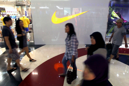Dita Alangkara  |  The Associated Press Indonesians walk past by a Nike store at a shopping mall in Jakarta, Indonesia. Workers for a Nike contractor in Indonesia say they've been physically and verbally abused for several years, with supervisors calling them