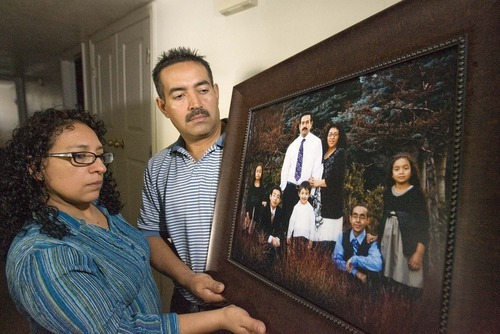 Paul Fraughton  |  The Salt Lake Tribune  Maribel and Rogelio Melgar, who recently lost their son Brayan to cancer, look at a family portrait taken before their son's death. Brayan  is wearing a blue shirt in the photo.