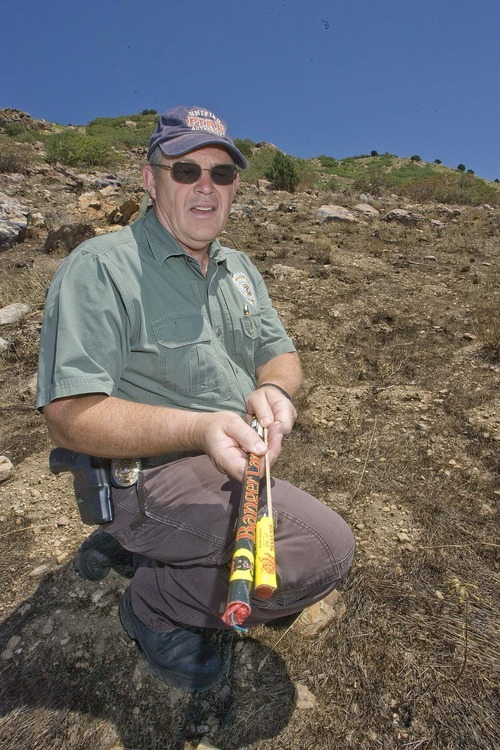 Paul Fraughton  |  The Salt Lake Tribune Unified Fire Authority investigator Ren Egbert, at the site of a hillside fire near Pete's Rock at the trailhead to Mt. Olympus, shows fireworks Thursday similar to the ones found at the scene.