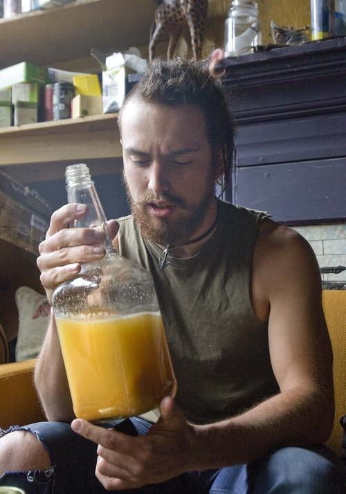 Paul Fraughton  |  The Salt Lake Tribune Matt DelPorto holds a bottle of kombucha tea that he added to orange juice.