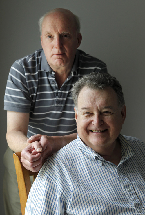 Jim Fitzgerald, top, stands next to his spouse Al Koski, seated front, as the two pose for a portrait in their home in Bourne, Mass., Thursday, July 21, 2011. Koski, 68, worked as a Social Security claims representative for more than 20 years before retiring in 2005. But even though he and Fitzgerald, 60, have been together for 36 years, and were legally married in Massachusetts in 2007, the federal government won't allow Fitzgerald to access Koski's federal pension. (AP Photo/Steven Senne)