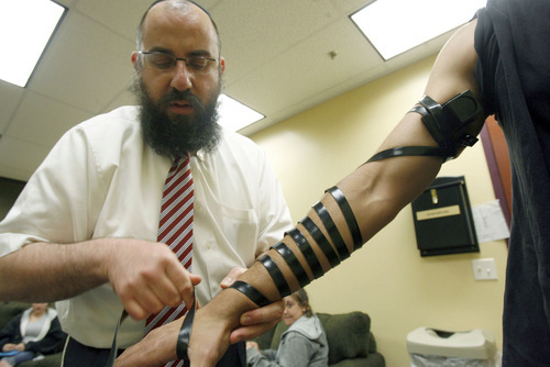 Francisco Kjolseth  |  The Salt Lake Tribune Rabbi Benny Zippel wraps the arm of  Netanel Kabaci, 16, in a Jewish ritual known as