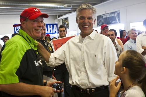 Chris Detrick | The Salt Lake Tribune  Presidential candidate Jon Huntsman talks with James Thurmond at Plaza Cycle Saturday July 16, 2011.