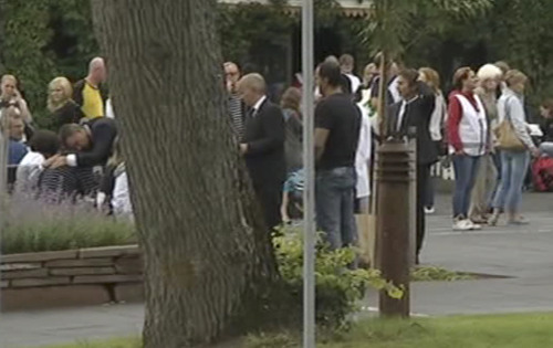 In this image from TV, Norway's Prime Minister Jens Stoltenberg, obscured behind tree at centre, bends down to comfort unidentified people outside a hotel where survivors are being reunited with family members in Sundvollen, Norway, Saturday, July 23, 2011.  A Norwegian dressed as a police officer gunned down at least 84 people at an island youth retreat before being arrested, police said Saturday. Investigators are still searching the surrounding waters, where people tried to flee from the attack, which followed an explosion in nearby Oslo city centre. (AP Photo) TV OUT