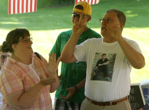 Leah Hogsten     The Salt Lake Tribune l-r Raphael Arruda's stepmother Jana De Souza, father Sergio De Souza and brother Andre Arruda lead  in singing