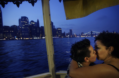 Nirvana Galvez, left, hugs her newlywed wife Ruth Galvez on a cruise hosted by Marriage Equality New York in New York, Sunday, July 24, 2011, as they pass by lower Manhattan. The couple are domestic partners where they live in California, but flew to New York to get married on the first day it became legal in the state. New York became the sixth and largest state to recognize same-sex weddings in a close state Senate vote on June 24 after strong lobbying by Cuomo and advocates. The first gay marriages in New York were performed just after midnight and continued through the day at municipal offices that opened for special weekend hours. (AP Photo/Seth Wenig)