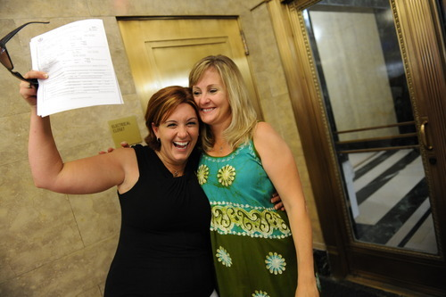 Kimberly Moreno, left,and Wendy Torrington show off their wedding certificate after being married at the City Clerk's Office in New York Sunday, July 24, 2011.  Hundreds of gay couples were expected to marry in New York and across the Empire State on the first day of same-sex marriage ceremonies. (AP Photo/David Handschuh, Pool)