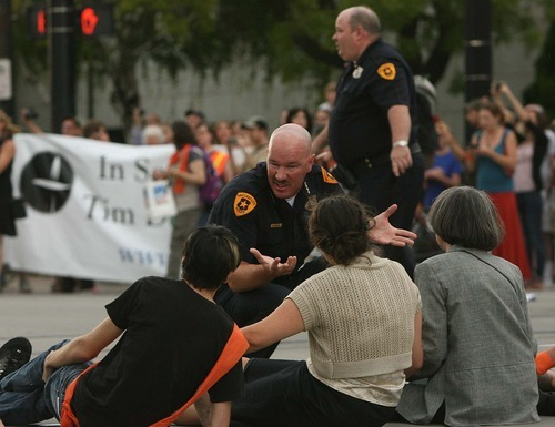 Leah Hogsten  |  The Salt Lake Tribune Salt Lake City Police Chief Chris Burbank explains the arrest procedure to protesters sitting in the middle of the intersection of  400 South and Main Street. Police arrested 26 people during a demonstration that blocked traffic along Main Street near the federal courthouse July 26 in Salt Lake City.