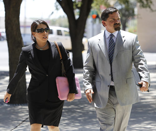 Emily Munoz Detoto, left, and Deric Walpole, right, defense attorneys for Polygamist leader Warren Jeffs arrive at the Tom Green County Courthouse, July 25, 2011, in San Angelo, Texas, where jury selection began Monday. Jeffs faces two counts of sexual assault of a child.  (AP Photo/Eric Gay)
