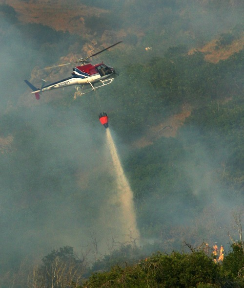 Steve Griffin  |  The Salt Lake Tribune  Firefighters, lower left, watch Wednesday as a helicopter drops a bucket of water on a hot spot of a wildfire burning above Farmington.