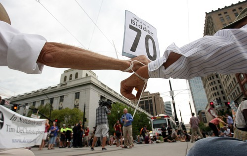 Steve Griffin     The Salt Lake Tribune   With their wrists zip tied together protestors hold hands as they block Main Street and 400 south following sentencing of Tim DeChristopher, who is also known as bidder 70,  at the federal courthouse in Salt Lake City, Utah Tuesday, July 26, 2011.
