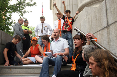 Leah Hogsten  |  The Salt Lake Tribune  Tim DeChristopher supporters sing songs while tied together with zip-ties outside federal court during his sentencing Tuesday, July 26, 2011. DeChrisptopher was sentenced to two years in prison and got a $10,000 fine for disrupting an oil lease auction in 2008.