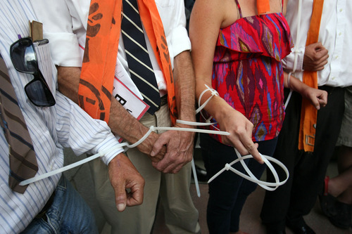 Leah Hogsten     The Salt Lake Tribune  Tim DeChristopher supporters zip-tied themselves together during DeChristopher's sentencing in federal court Tuesday, July 26, 2011. DeChrisptopher was sentenced to two years in prison and got a $10,000 fine for disrupting an oil lease auction in 2008.