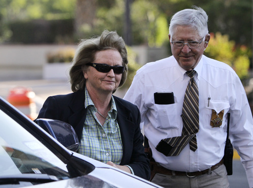 Tony Gutierrez  |  The Associated Press  District Judge Barbara Walther arrives at the Tom Green County Courthouse escorted by a law enforcement official Thursday in San Angelo, Texas. Walther is presiding over the trial of Polygamist sect leader Warren Jeffs.