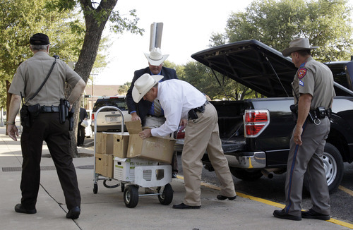 Tony Gutierrez  |  The Associated Press  Law enforcement officials unload boxes of documents related to trial of polygamist leader Warren Jeffs at the Tom Green County Courthouse in San Angelo, Texas, on Thursday.