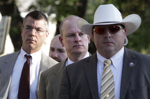Tony Gutierrez  |  The Associated Press  Lead prosecutor for the state Eric Nichols, center, arrives with a member of his team, left, escorted by law enforcement officials at the Tom Green County Courthouse in San Angelo, Texas, on Friday. Jeffs is charged with two counts of sexual assault of a child at a compound south of the oil and gas town of San Angelo.