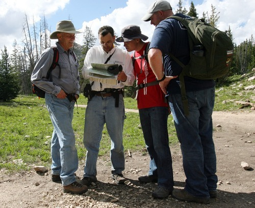 Steve Griffin  |  The Salt Lake Tribune  Aaron Schellenberg, second from left,  looks at a map with his father Al Schellenberg, left, his brother Matthew Schellenberg and brother in-law Buck Gay, right,  as they search for Aaron's son Joseph Schellenberg who went missing from his camp site on Long Lake two miles above the Crystal Lake Trailhead in the Unita Mountains above Kamas, Utah Tuesday, August 2, 2011.