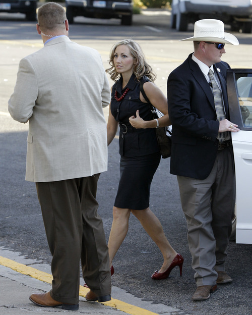 Rebecca Musser, center, a former member of the Fundamentalist Church of Jesus Christ of Latter Day Saints arrives escorted by law enforcement officials at the Tom Green County Courthouse, in San Angelo, Texas, for court proceedings in the sexual assault trial  against polygamist leader Warren Jeffs on Thursday, Aug. 4, 2011.   Jeffs, 55, is accused of sexually assaulting two girls he took as brides during so-called