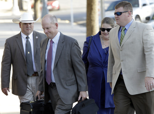 Lead prosecutor in the Warren Jeffs sexual assault trial Eric Nichols, second from left, and members of his team are escorted into the Tom Green County Courthouse, in San Angelo, Texas, on Thursday, Aug. 4, 2011.  Jeffs, 55, is accused of sexually assaulting two girls he took as brides during so-called