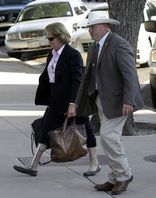 Barbara Walther, 51st District judge, arrives escorted by a law enforcement official at Tom Green County Courthouse in San Angelo, Texas, on Thursday, Aug. 4, 2011. Walther is presiding over the sexual assault trial against Polygamist religious leader Warren Jeffs.  (AP Photo/Tony Gutierrez)