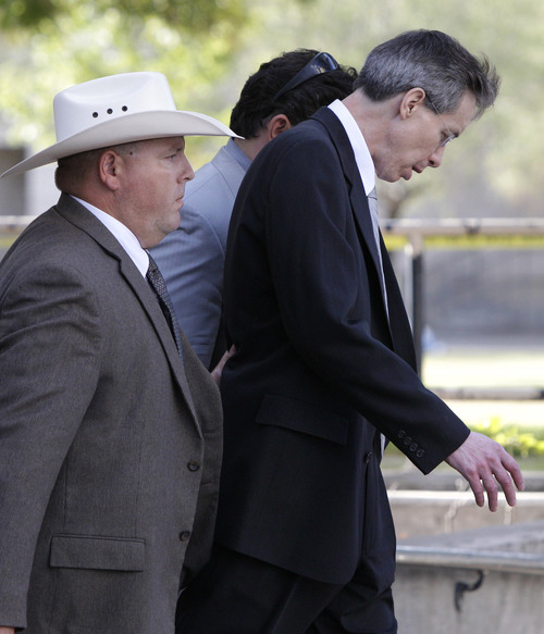 A law enforcement officer, left, escorts Polygamist religious leader Warren Jeffs, center, and his defense advisor Deric Walpole, rear, out of the Tom Green County Courthouse Thursday Aug. 4, 2011, in San Angelo, Texas. A jury convicted Jeffs of child sexual assault Thursday, in a case stemming from two young followers he took as brides in what his church calls