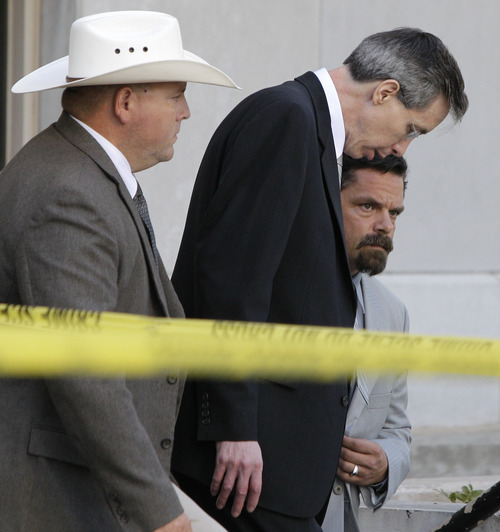 A law enforcement officer, left, escorts Polygamist religious leader Warren Jeffs, center, and his defense advisor Deric Walpole out of the Tom Green County Courthouse Thursday Aug. 4, 2011, in San Angelo, Texas. A jury convicted Jeffs of child sexual assault Thursday, in a case stemming from two young followers he took as brides in what his church calls
