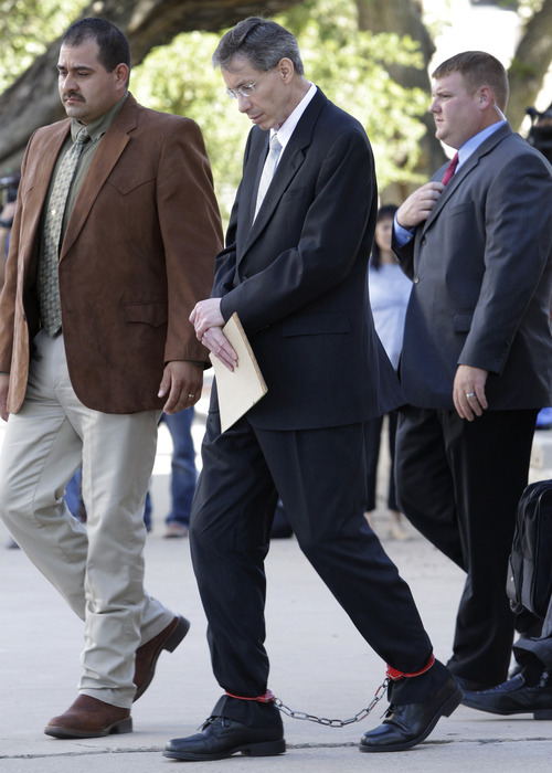Law enforcement officials, left, and right, escort Warren Jeffs, center, out of the  Tom Green County Courthouse in ankle and wrist shackles Friday Aug. 5, 2011, in San Angelo, Texas.  Jeffs, a polygamist sect leader convicted of child sexual assault walked out of his sentencing hearing in protest Friday, after reading a statement he claimed was from God. The statement promised a