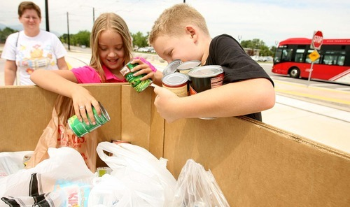 LEAH HOGSTEN  |  The Salt Lake Tribune Kayla Harr, 8, center and her brother Jon, 10, place cans of vegetables into a bin in exchange for a ride Wednesday aboard TRAX with their mother, Stacey Harr (left). TRAX riders on the new West Valley and Mid-Jordan lines donated food in exchange for free preview rides.