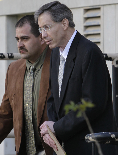 FILE- In this Aug. 5, 2011 file photo, Warren Jeffs, right, is escorted out of the Tom Green County Courthouse by a law enforcement officer, left, in San Angelo, Texas. Jeffs' Texas sexual assault conviction is considered a victory for prosecutors and former church members who revile him. But it may not mean much for the future of his church and the blindly faithful who follow him. Members of the Fundamentalist Church of Jesus Christ of Latter Day Saints still revere him as a prophet, God's voice on earth, even though he was convicted for having sex with sect girls as young as 12. (AP Photo/Tony Gutierrez, File)