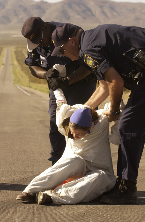 Joe Cavaretta  |  Associated Press file photo Nevada Sate Police troopers arrest a protester who crossed the line into the Nevada Test Site at Mercury, Nev., about 70 miles north of Las Vegas, Sunday, May 11, 2003. Thirty-four protesters opposed to the proposed Yucca Mountain nuclear storage facility and weapons testing  were arrested for trespassing.