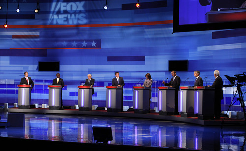 Republican presidential candidates, from left, former Pennsylvania Sen. Rick Santorum, businessman Herman Cain, Rep. Ron Paul, R-Texas, former Massachusetts Gov. Mitt Romney, Rep. Michele Bachmann, R-Minn., former Minnesota Governor Tim Pawlenty, former Utah Gov. Jon Huntsman, and former House Speaker Newt Gingrich are seen during the Iowa GOP/Fox News Debate at the CY Stephens Auditorium in Ames, Iowa, Thursday, Aug. 11, 2011. (AP Photo/Charlie Neibergall, Pool)