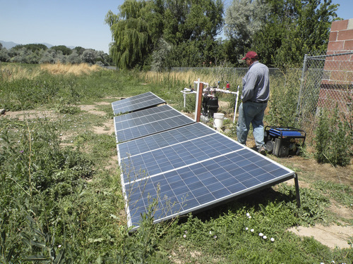 Erin Alberty | The Salt Lake Tribune Thayne Tagge demonstrates the solar-powered pump for the irrigation system at his farm in Holladay. Salt Lake County leased the land as part of its urban farming initiative.