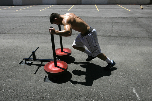 Scott Sommerdorf  |  The Salt Lake Tribune Mixed Martial Arts fighter Rad Martinez of West Jordan pushes a weighted sled 40 yards across the parking lot fifteen times as part of his MMA training session at the Riven Academy in Orem, Thursday, August 11, 2011.