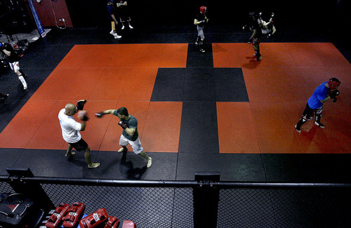 Scott Sommerdorf  |  The Salt Lake Tribune MMA fighter Rad Martinez of West Jordan (lower left), spars during a training session with coach Jason Mertlich at the Riven Academy in Orem, Thursday, August 11, 2011.