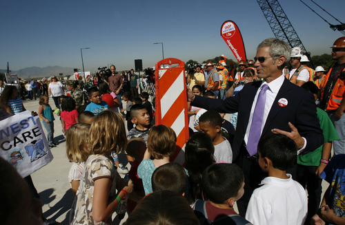 Francisco Kjolseth  |  The Salt Lake Tribune Mayor Ralph Becker gets a little help setting up the celebratory traffic cone from Northwest Child Center kids as they celebrate the opening of the rebuilt North Temple Viaduct on Wednesday, August 17, 2011. Construction of the light rail portion will continue with an expected projected opening of the Airport TRAX line in 2013.