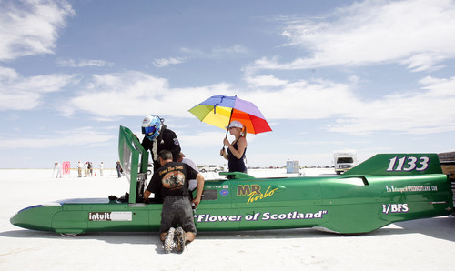 Rick Egan   |  The Salt Lake Tribune  Anna Plaszajski holds an umbrella, as Rick Pearson prepares for a run on the Salt Flats in his car