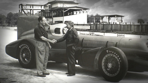 Racer Ab Jenkins (left) and legendary auto engineer August Duesenberg shake hands in front of their creation, the Mormon Meteor III, in 1938 at the Indianapolis Motor Speedway. The image is seen in the documentary