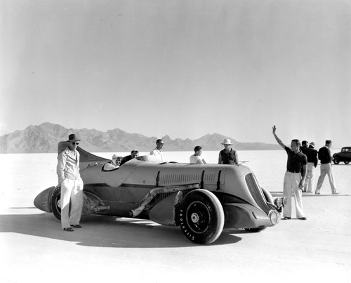 Ab Jenkins sits behind the wheel of his original Mormon Meteor, the landspeed record car that raced the Bonneville Salt Flats in 1937, with Ab's son Marv standing by the tail fin. (The car was originally Ab's stock 1935 Duesenberg Special, later equipped with a 1924 12-cylinder Curtis Conquerer aircraft engine and other aerodynamic features.) The image is seen in the documentary