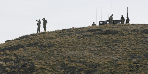 Scott Sommerdorf  |  Salt Lake Tribune SUSAN POWELL SEARCH National Guard personnel point as they survey an area near Simpson Springs. Many people came together to help in the search for any sign of Susan Powel, Saturday 4/10/10.