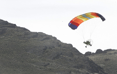 Scott Sommerdorf     Salt Lake Tribune SUSAN POWELL SEARCH Volunteer searcher Dan Despain (cq) flies his flying parachute over rough terrain as he helps scour the areas in and around Simpson Springs Saturday, 4/10/10.