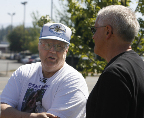 Rick Egan   |  The Salt Lake Tribune Chuck Cox, left, father of Susan Powell, exchanges words with Steve Powell, father of Joshua Powell, at a shopping center in Puyallup, Wash., on Saturday.