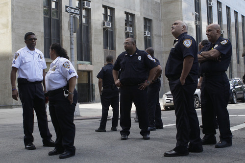 Court officers stand outside Manhattan Criminal court building in New York on Tuesday, Aug. 23, 2011 after it was evacuated following an earthquake. (AP Photo/Mary Altaffer)